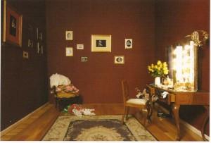 Tocador, cadeiras, cabide, peças de vestuário, adereços, flores e fotografias a preto e branco, dimensões variáveis